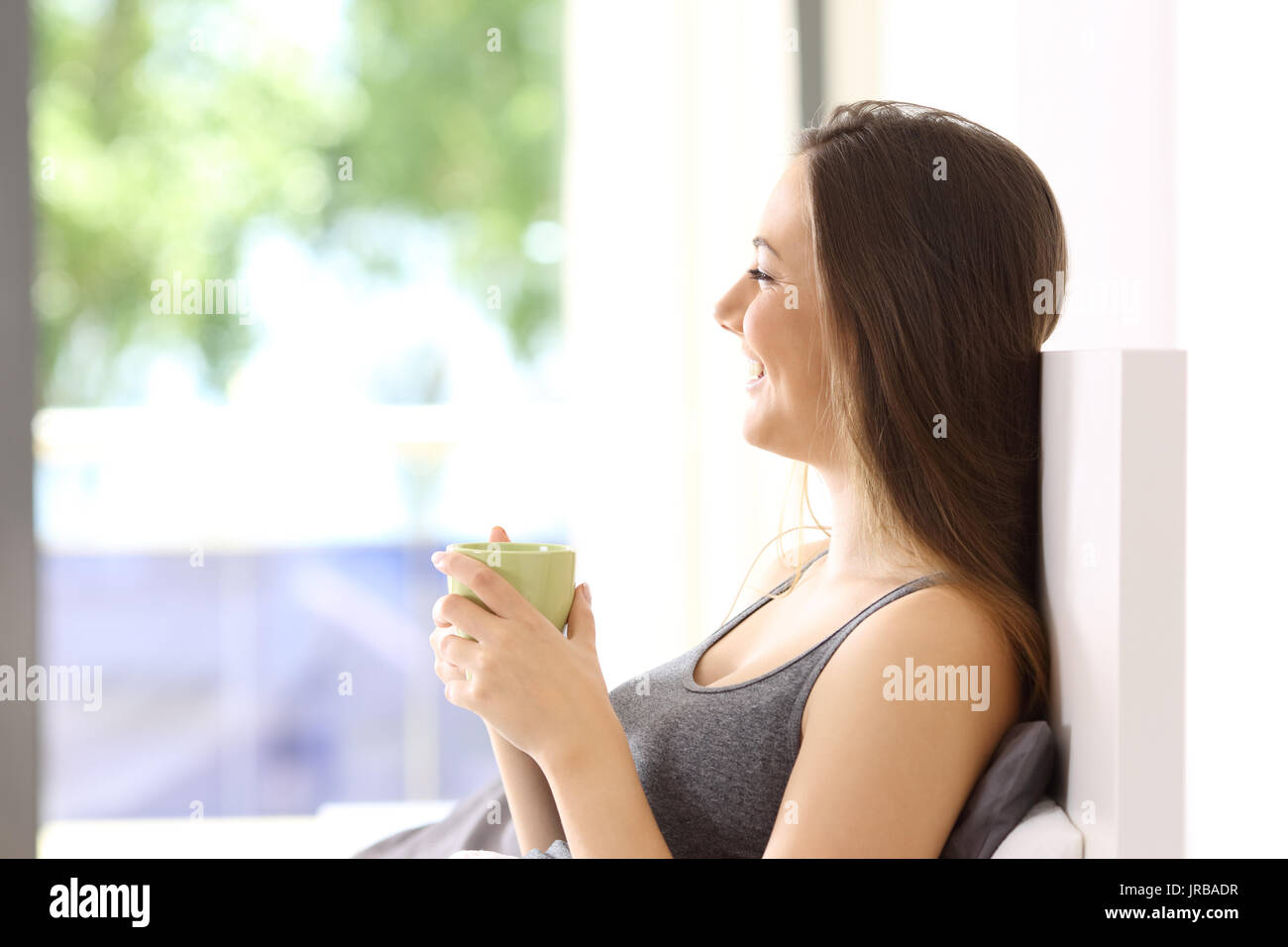 Side view of a happy single woman having breakfast on the bed of an hotel room or apartment - Stock Image