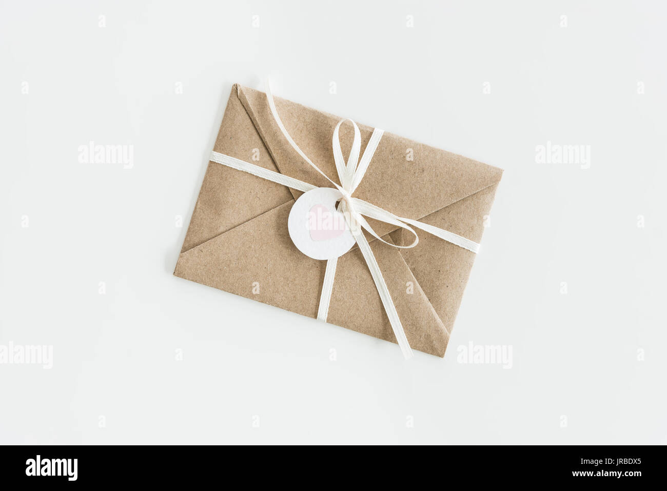 Kraft Envelope With Teg With Heart And Ribbon Isolated On White