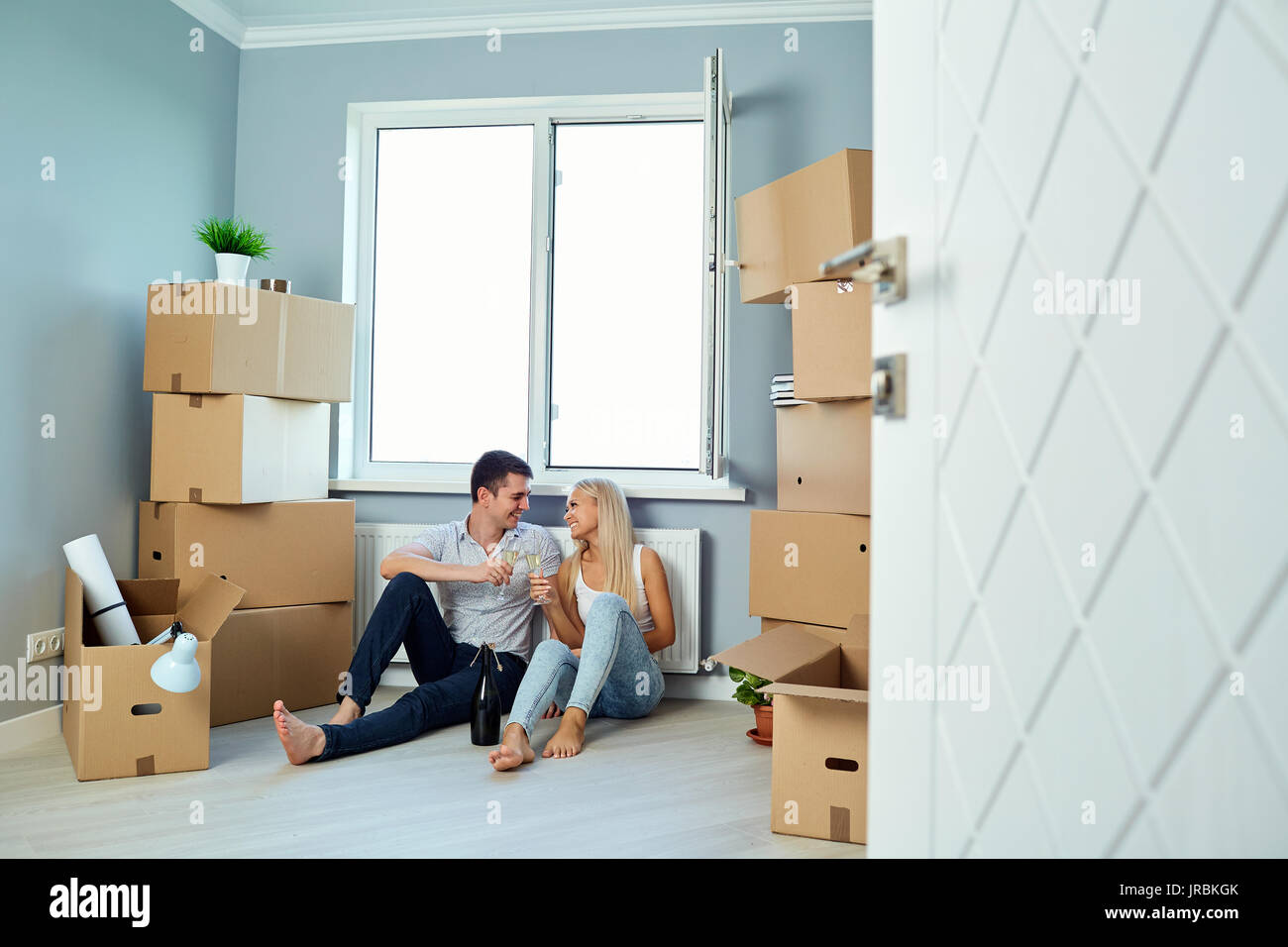 Happy couple with champagne in the room for a housewarming - Stock Image