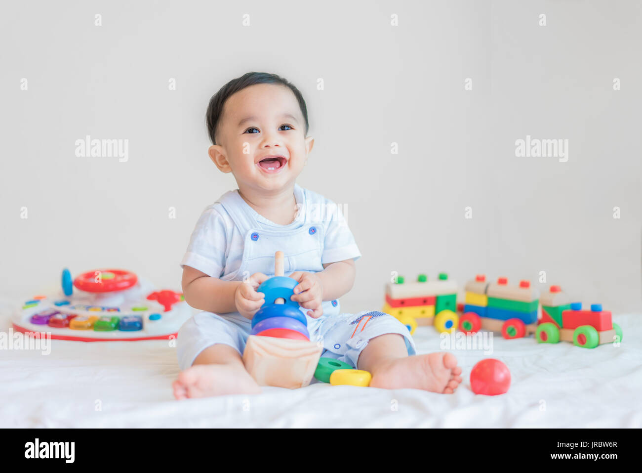 Adorable Asian baby boy 9 months sitting on bed and playing with color developmental toys at home. - Stock Image