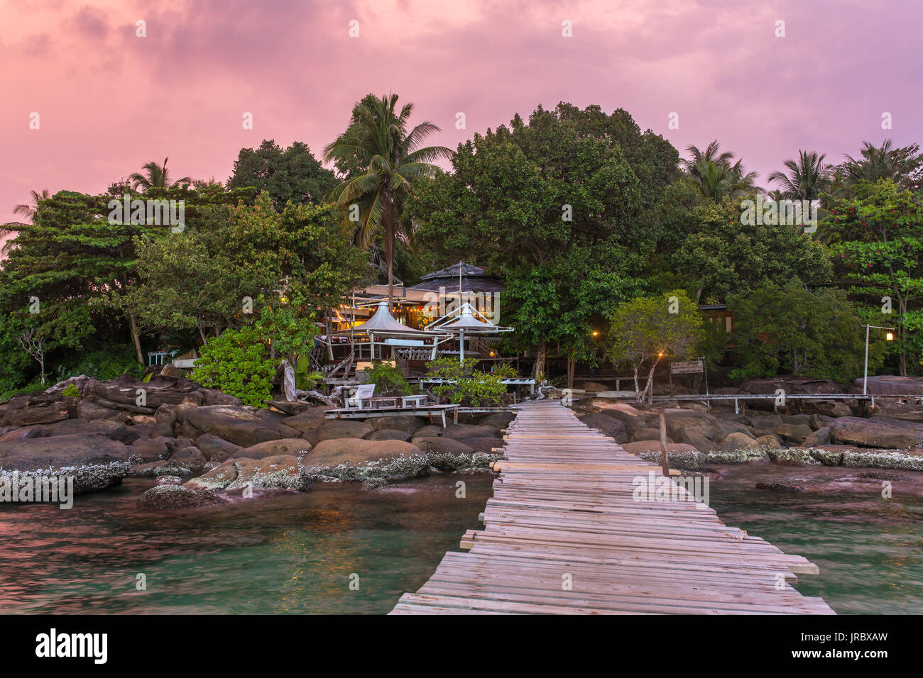 Wooden pier to a tropical island resort on Koh Kood island during sunset, Thailand. - Stock Image