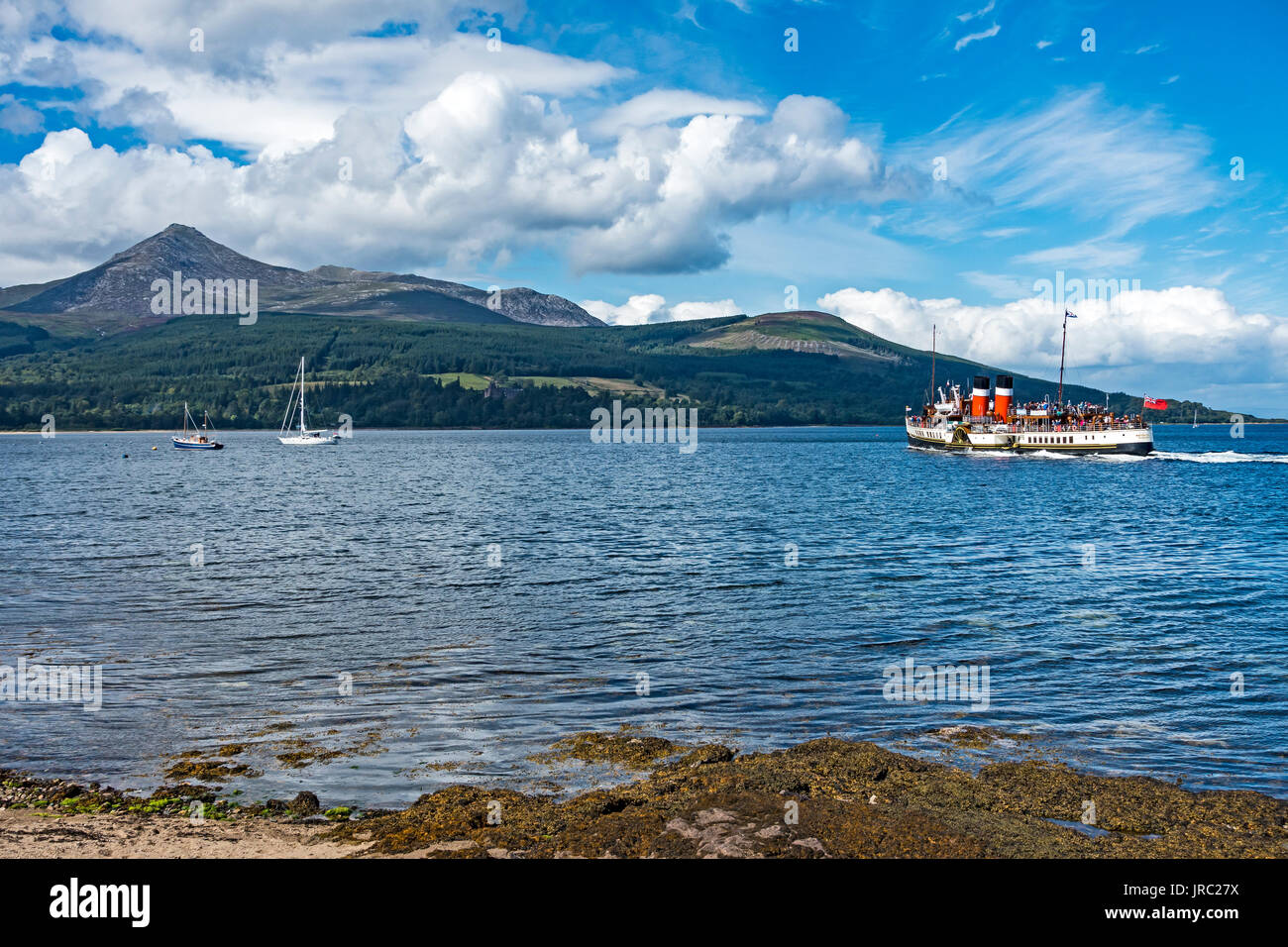 Ocean going paddle steamer Waverley departing Brodick Arran Argyll & Bute Scotland UK with Goat Fell mountain left. - Stock Image