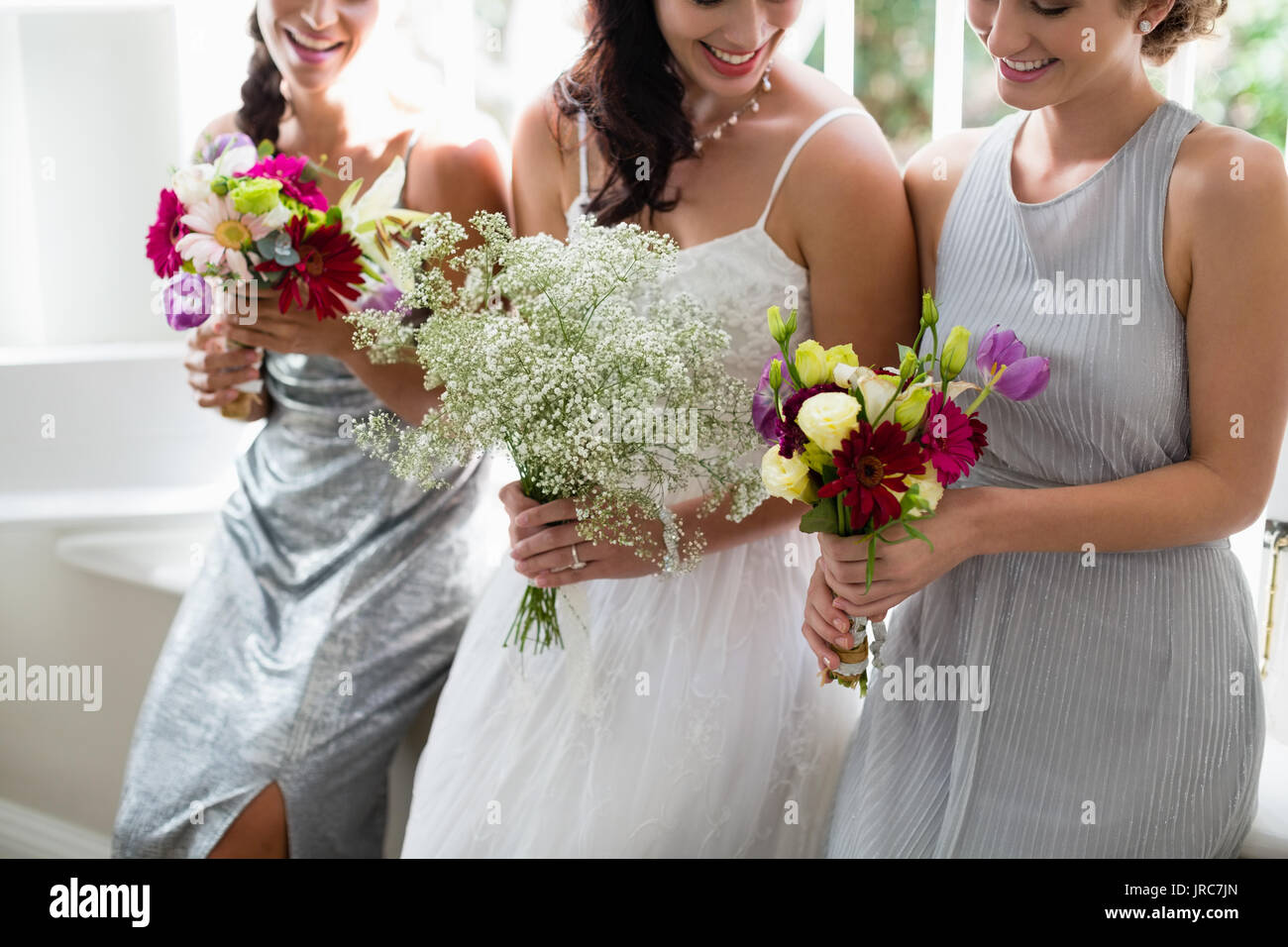 Bride and bridesmaids standing with bouquet at home Stock Photo