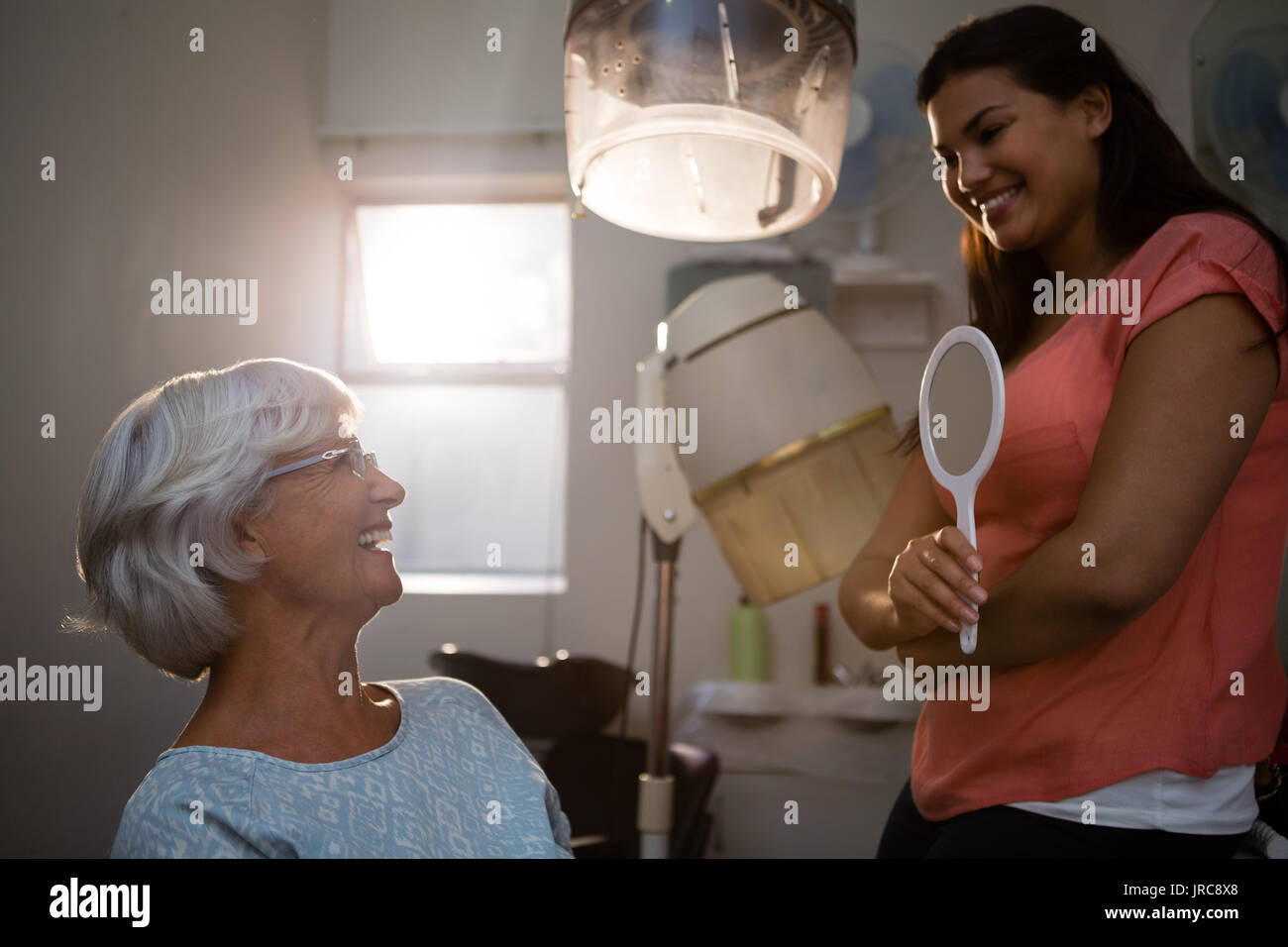 Hairstylist talking to senior woman in salon - Stock Image