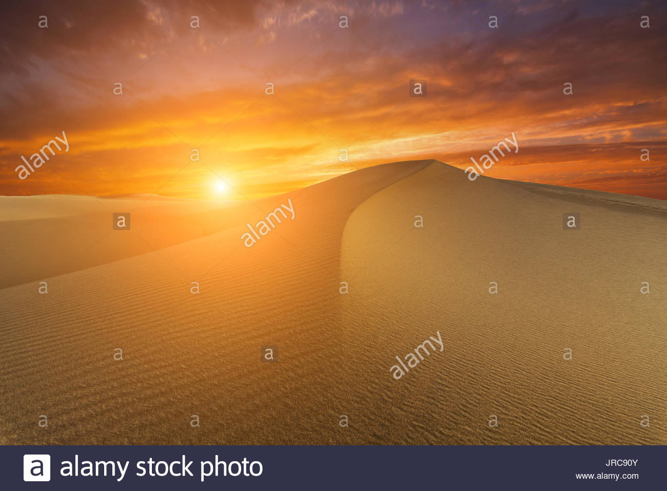 Beautiful desert landscape on the background of a fiery sunset. - Stock Image