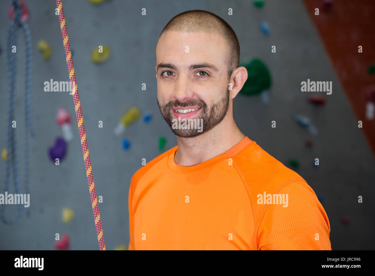 Portrait of trainer standing with rope in fitness studio - Stock Image