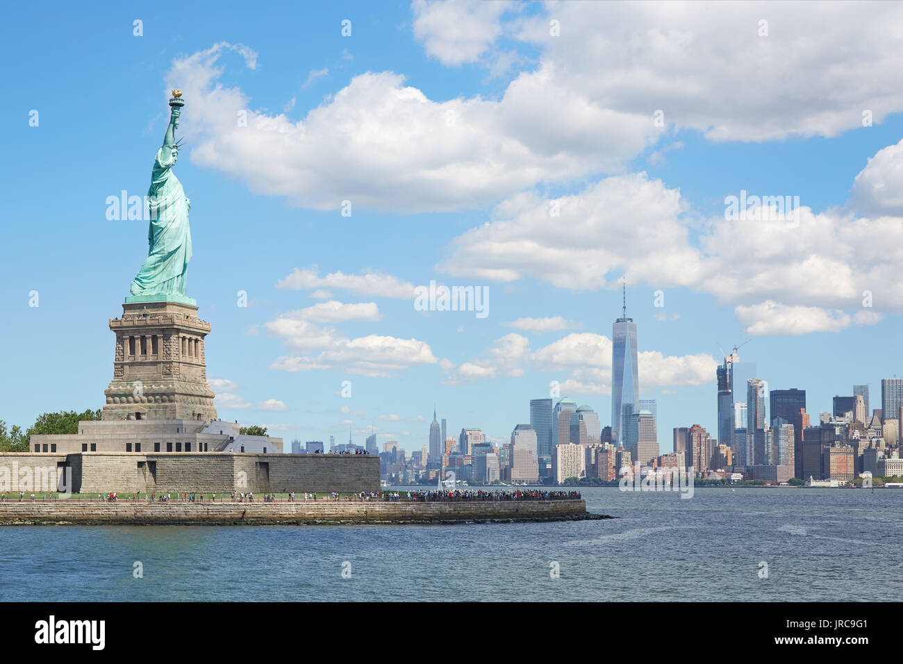 Statue of Liberty island and New York city skyline in a sunny day, white clouds Stock Photo