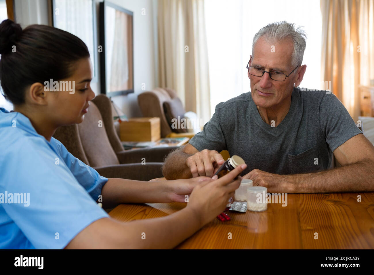 Female doctor guiding senior man in taking medicine at table - Stock Image