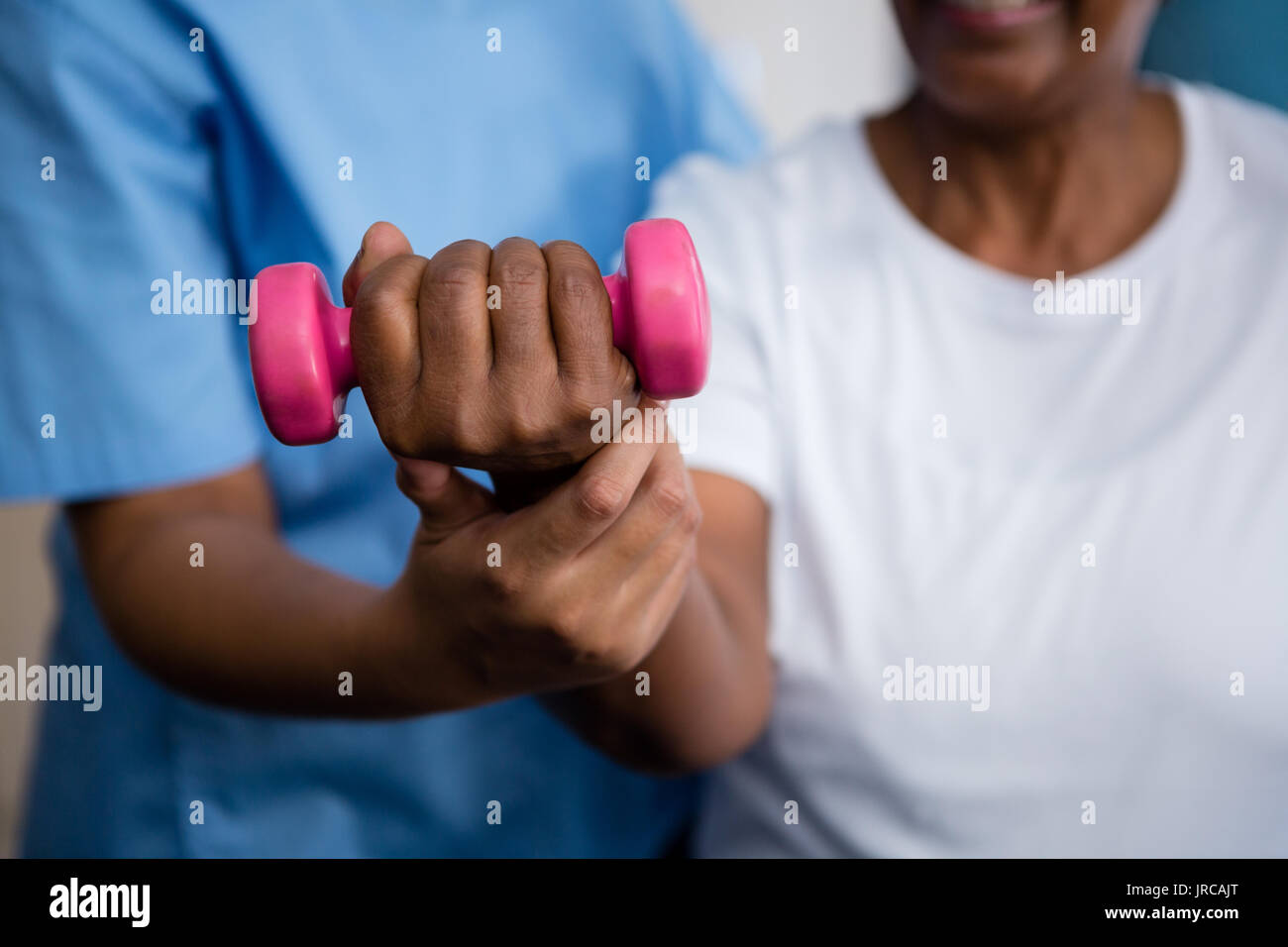Midsection of nurse guiding senior woman in lifting dumbbell at retirement home - Stock Image