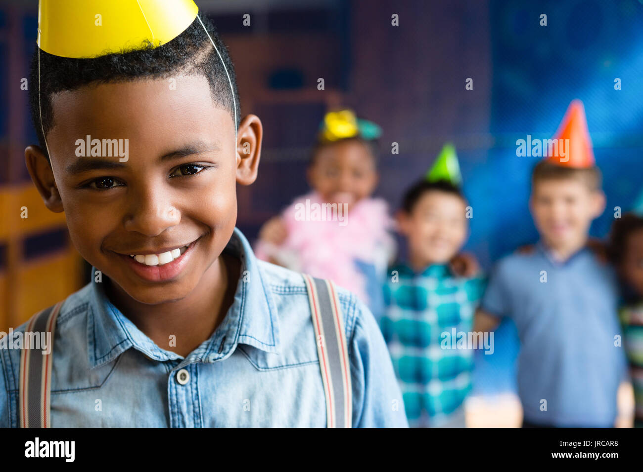 Portrait of boy wearing suspenders with friends in background during birthday party - Stock Image