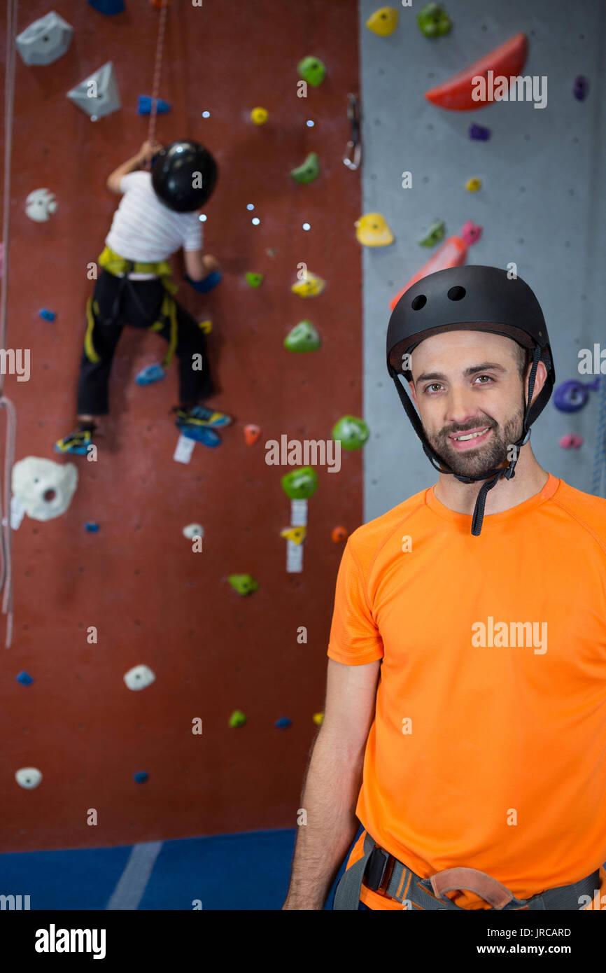 Portrait of trainer standing in fitness studio - Stock Image