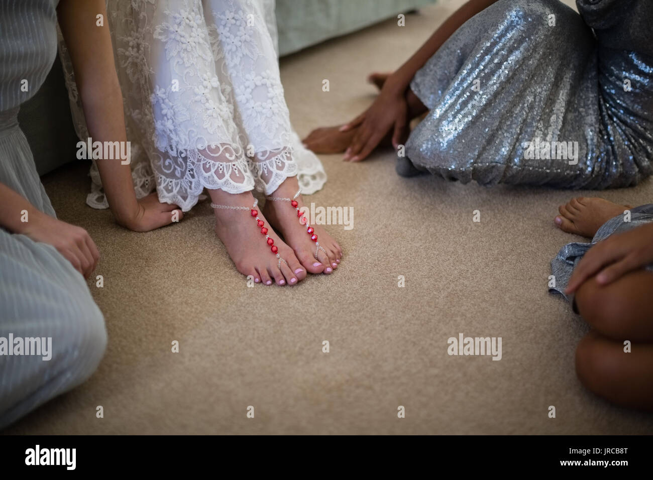 Bride and bridesmaids sitting together at home Stock Photo