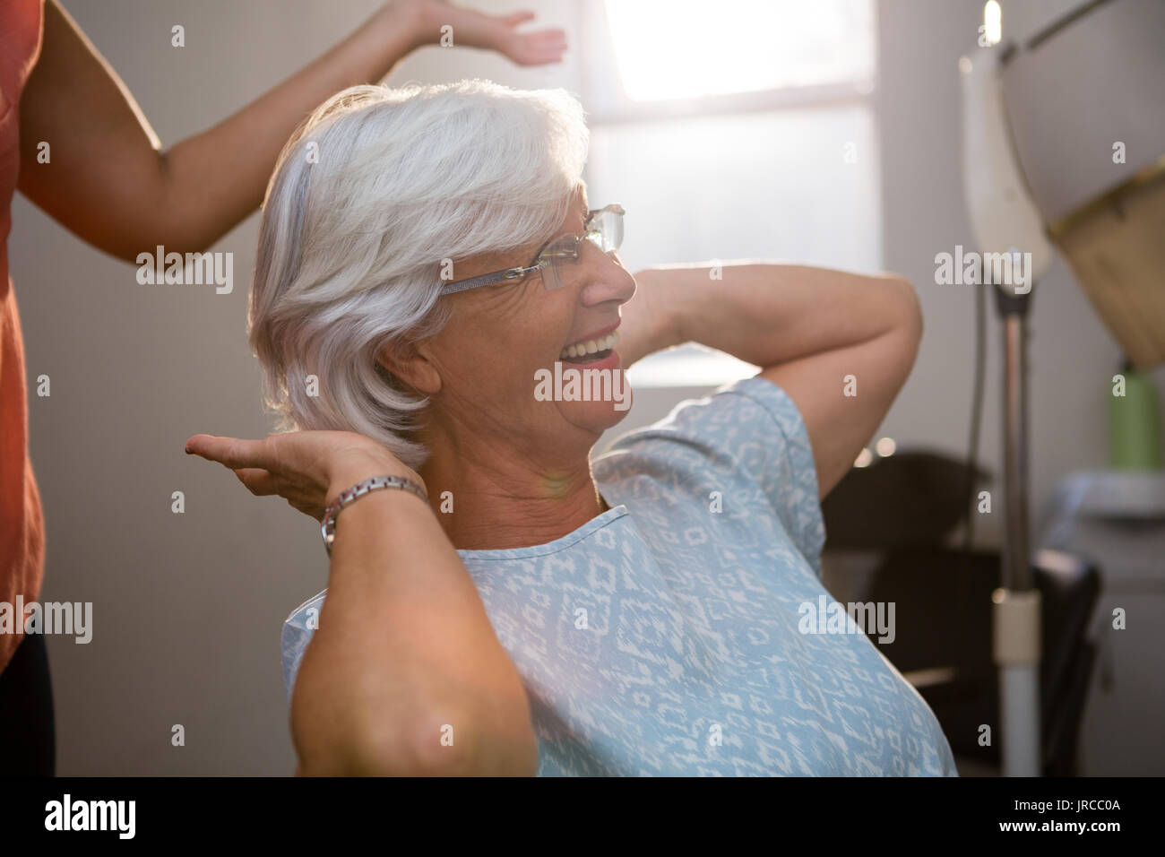 Midsection of hairstylist standing by happy senior woman at salon - Stock Image