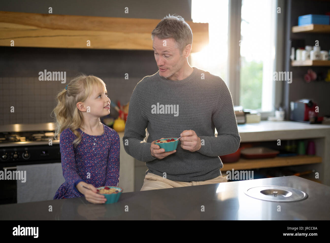 Little girl and father looking at each other while eating fruits from a bowl in the kitchen - Stock Image