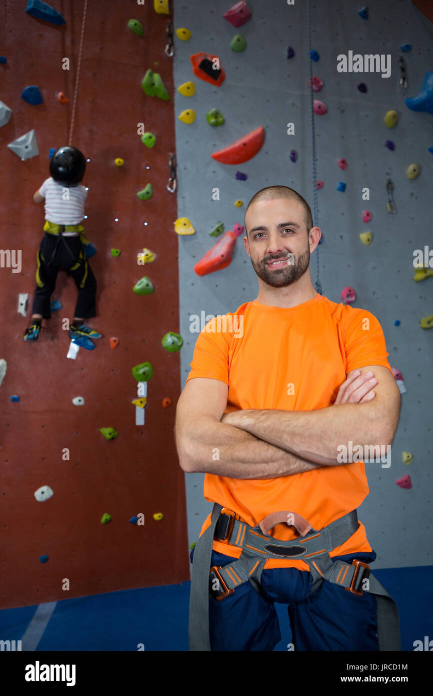 Portrait of trainer standing with arms crossed in fitness studio Stock Photo