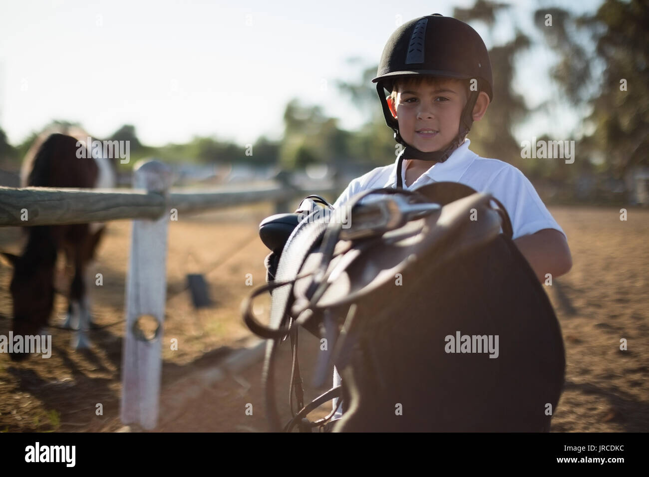 7836dc5264c0 Boy Holding Saddle Stock Photos   Boy Holding Saddle Stock Images ...