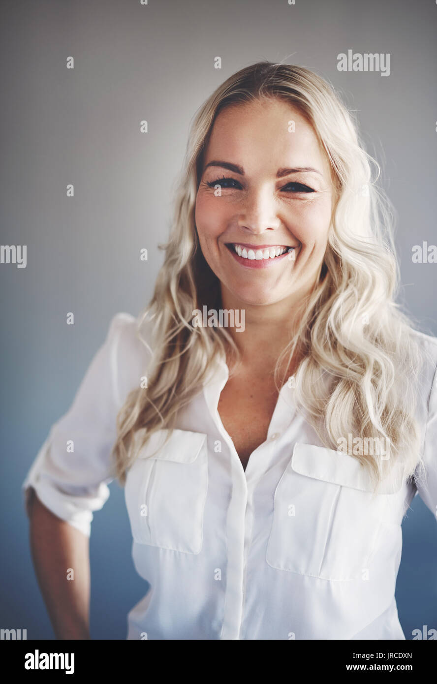 Portrait of a smiling young businesswoman with blonde hair standing alone in an office with her hands on her hips - Stock Image