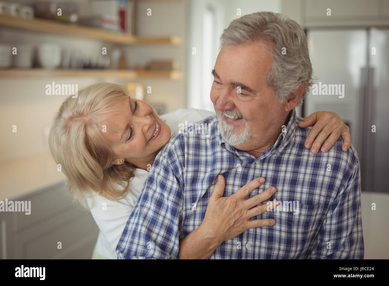 Senior couple hugging each other at home Stock Photo
