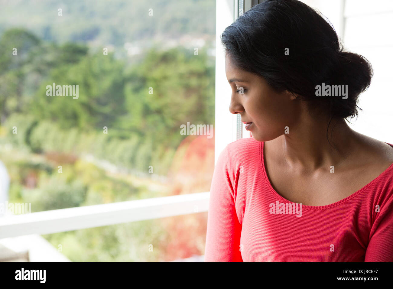 Thoughtful young woman looking through window at home - Stock Image