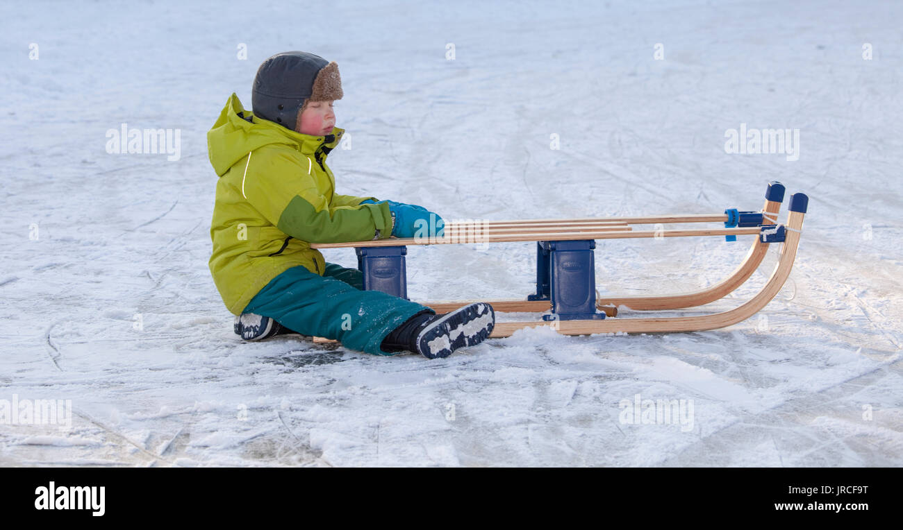 THE NETHERLANDS-FEB 4:Small tired boy sitting on ice with red cheeks holding on to his sleigh on feb 4, 2012. February is the coldest month throughout - Stock Image
