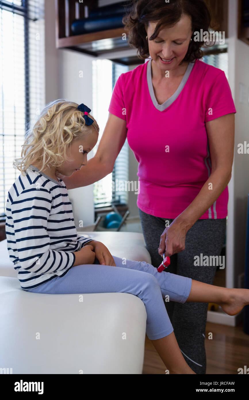 Doctor examining reflexes of patient knee in clinic Stock Photo