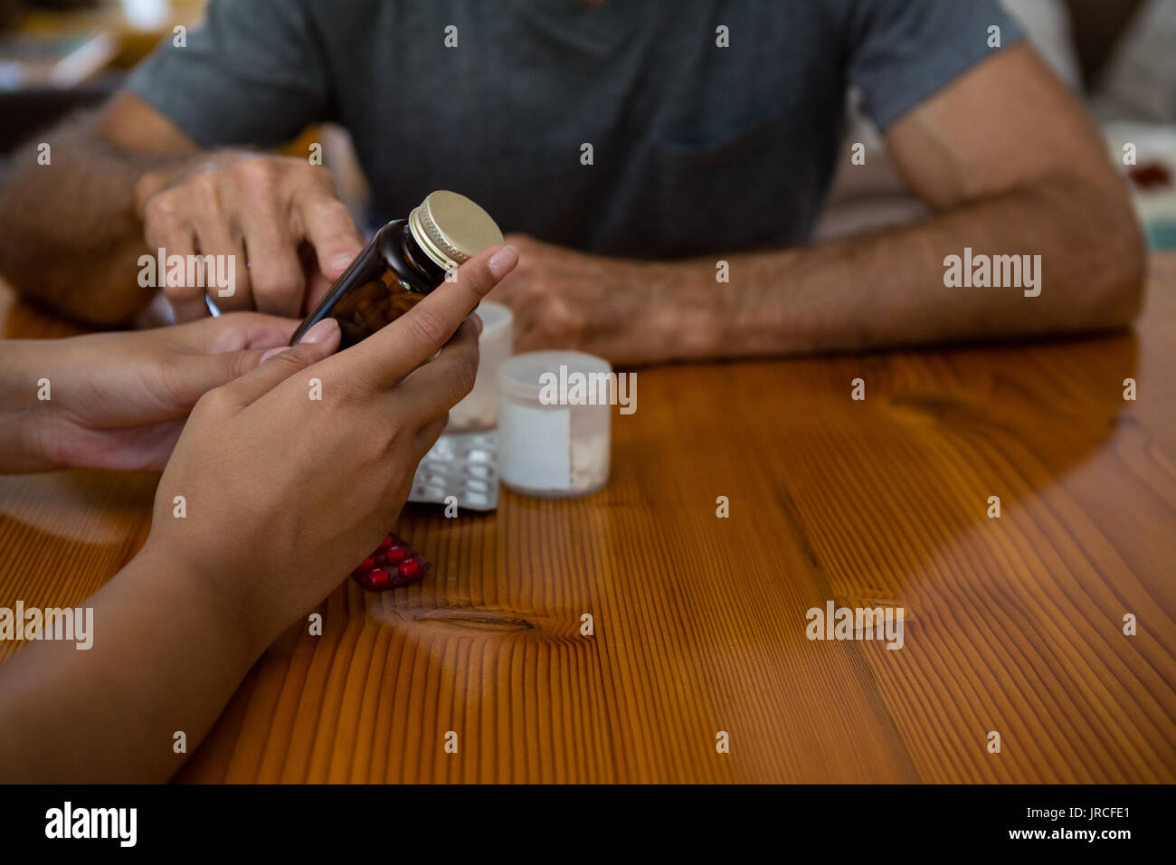 Midsection of doctor guiding senior man in taking medicine at table - Stock Image