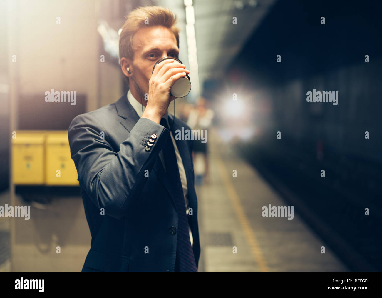 Young businessman drinking a coffee and listening to music on his cellphone while standing on a subway platform during his morning commute - Stock Image