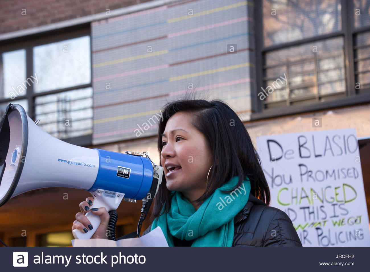 A Chinese-American activist speaks in protest over the shooting death of Akai Gurley, shot by Chinese-American NYPD rookie officer Peter Liang. - Stock Image