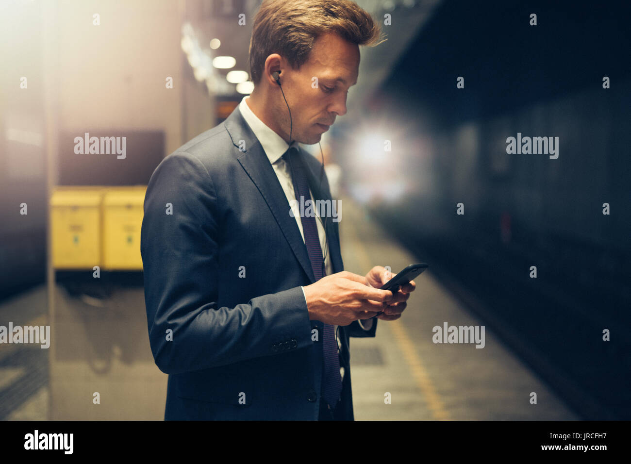 Young businessman wearing earphones and reading text messages on his cellphone while standing on a subway platform during his morning commute - Stock Image