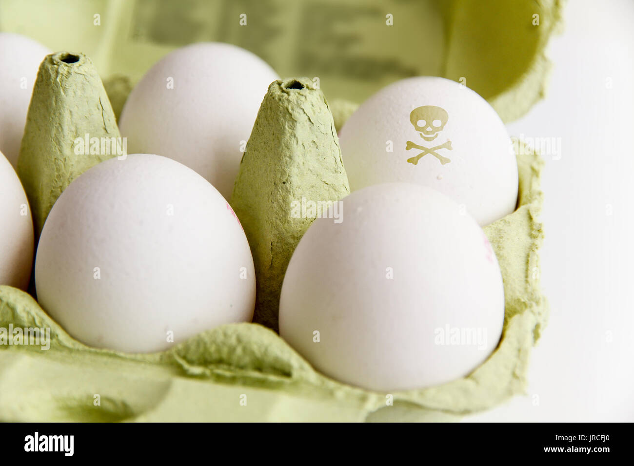 Eggs in a package with one egg painted with a poisonous risk symbol skull and bones. Image concept for food contamination, tainted eggs scandal. - Stock Image