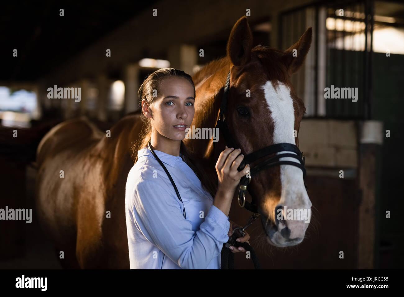 Portrait of female vet stroking horse at stable - Stock Image