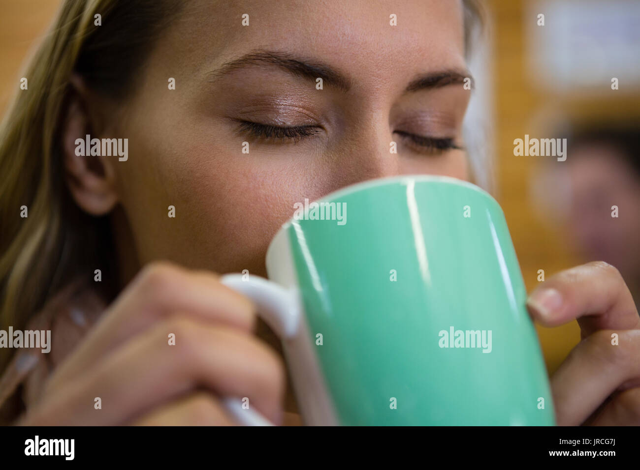 Close up of young woman with eyes closed drinking coffee at cafe - Stock Image
