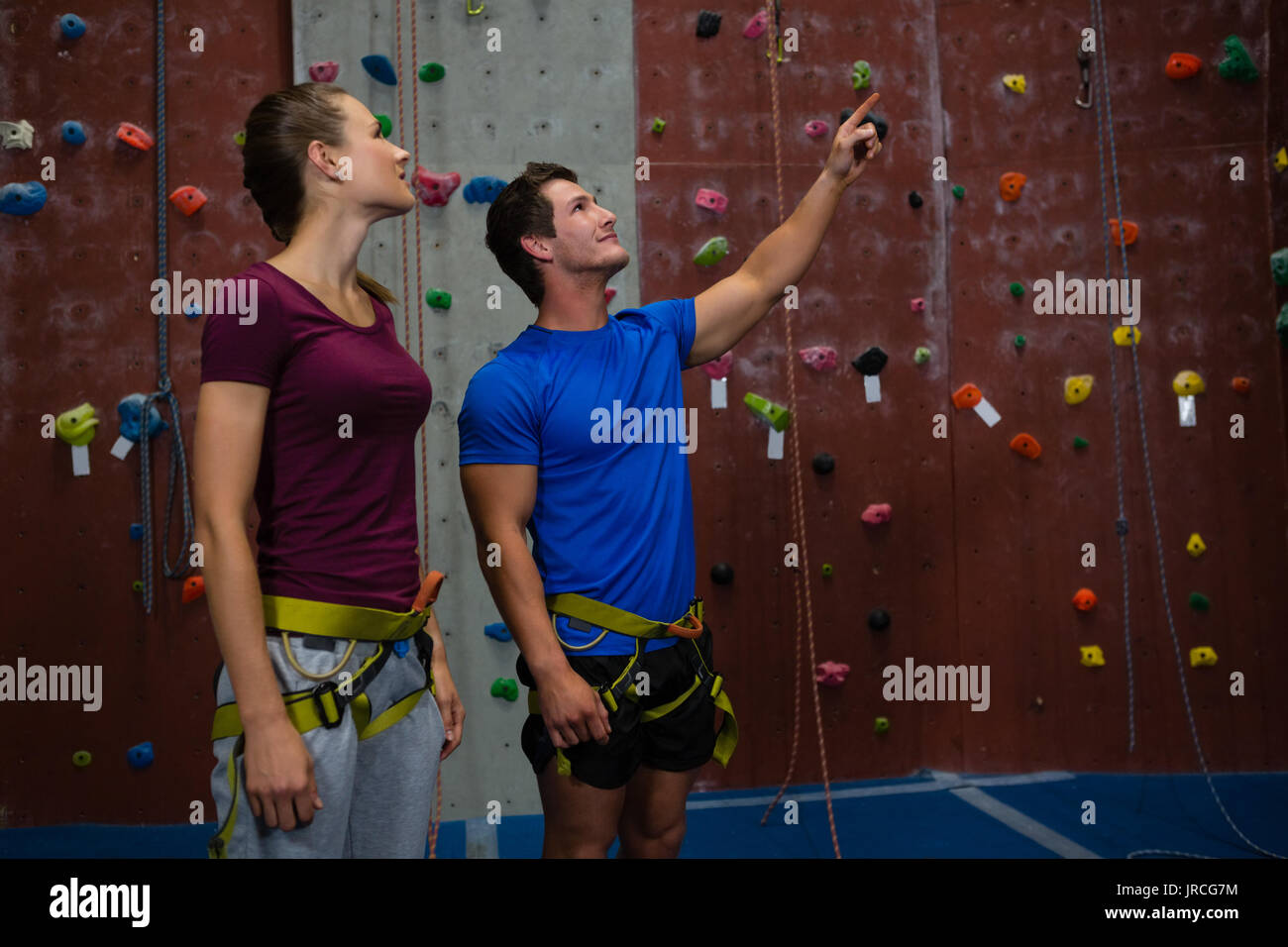 Male trainer guiding athlete in climbing wall at gym - Stock Image
