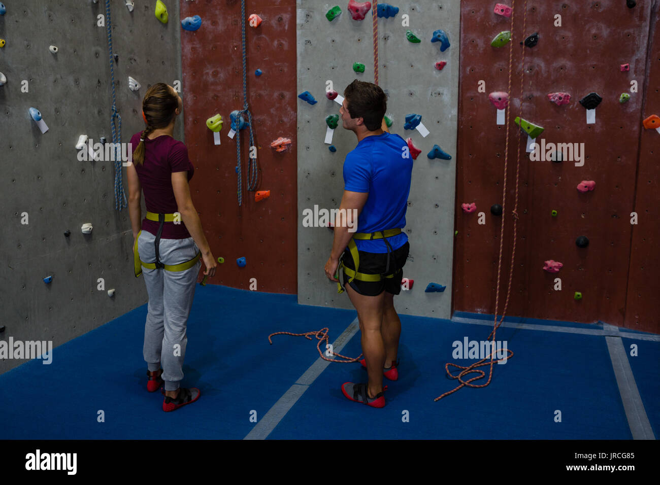 Full length of male trainer guiding woman in climbing wall at gym - Stock Image