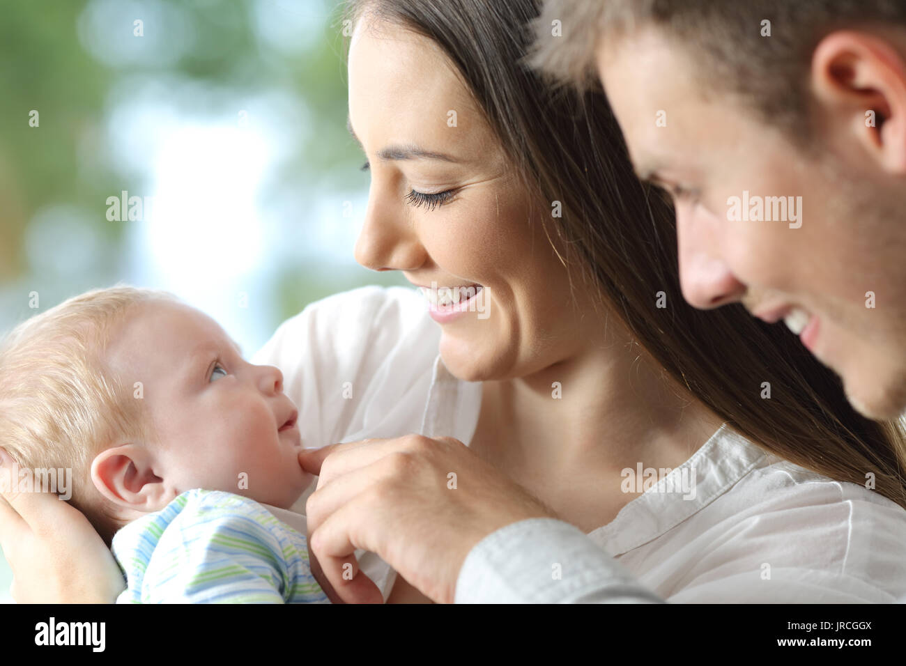Proud parents holding their baby an looking him - Stock Image