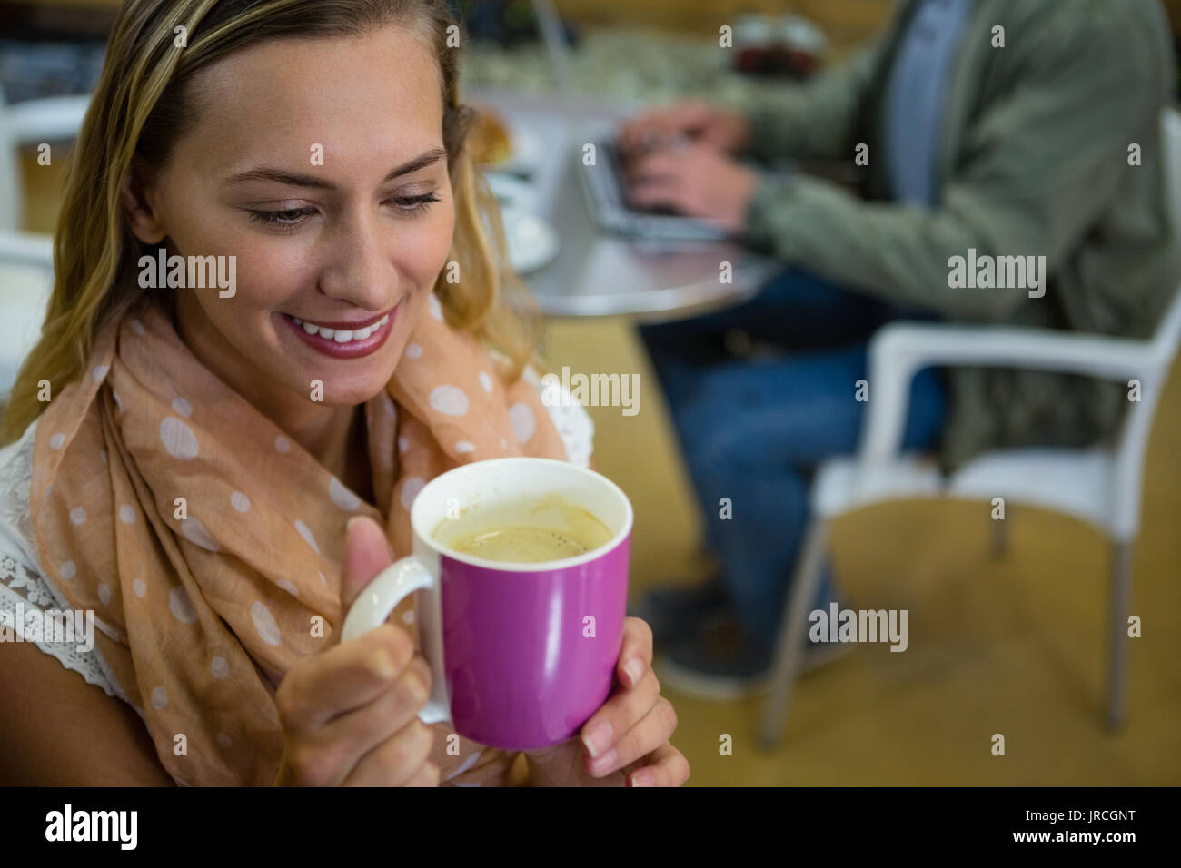 High angle close up of young woman holding coffee cup in gym - Stock Image