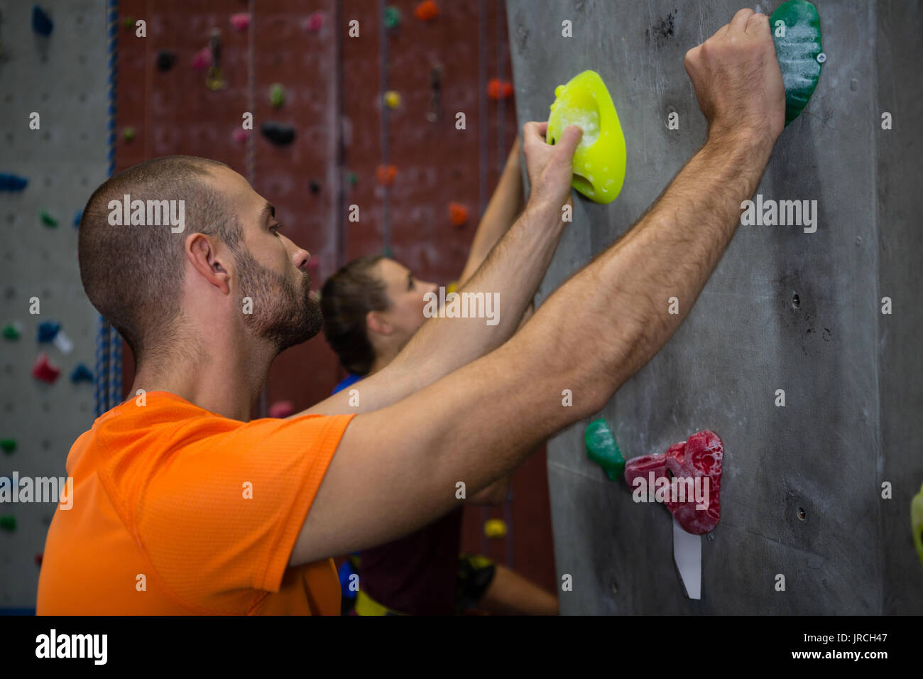 Side view of male trainer guiding athlete in climbing wall at health club - Stock Image