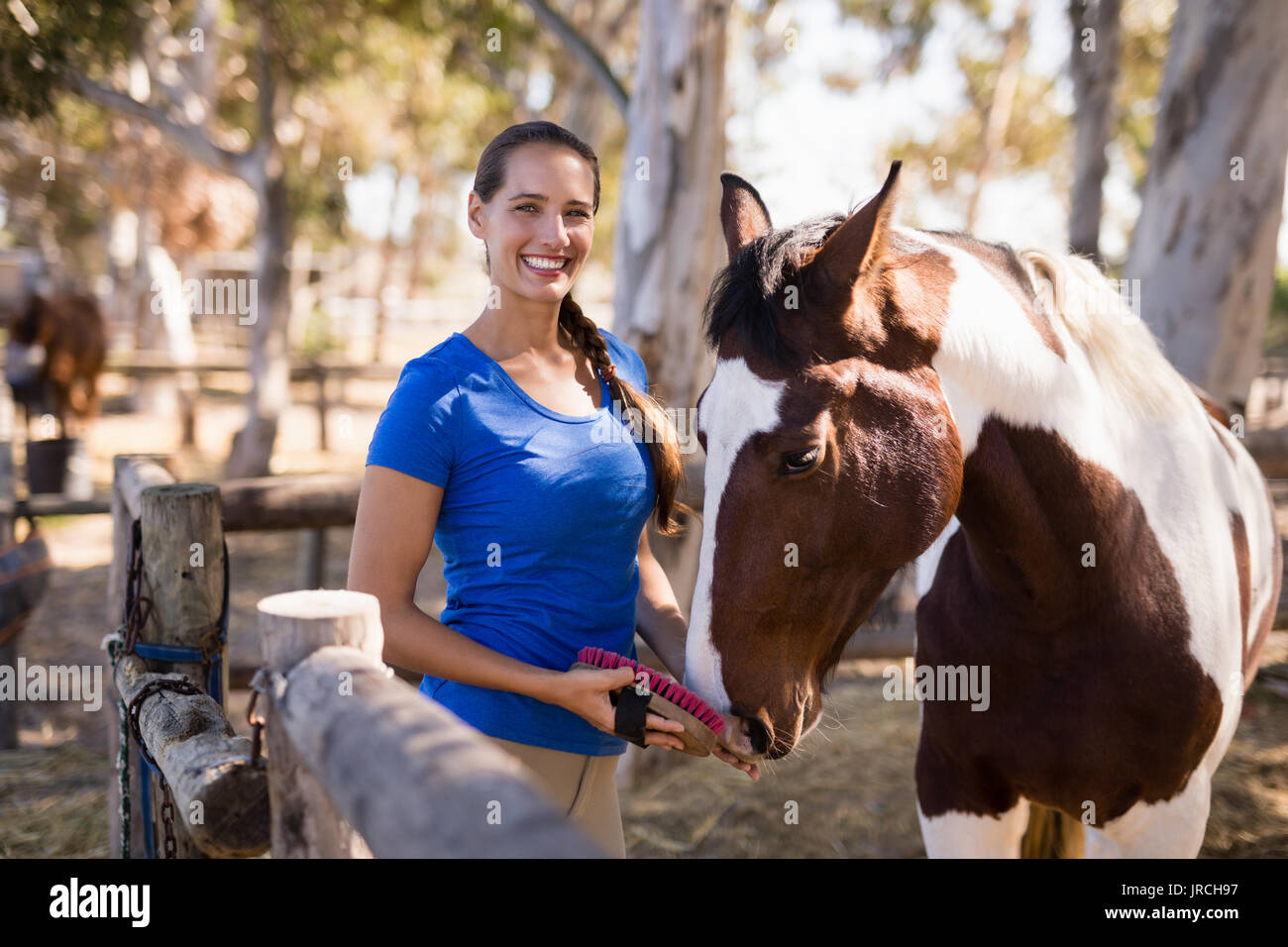 Portrait of female jockey cleaning horse while standing at paddock Stock Photo