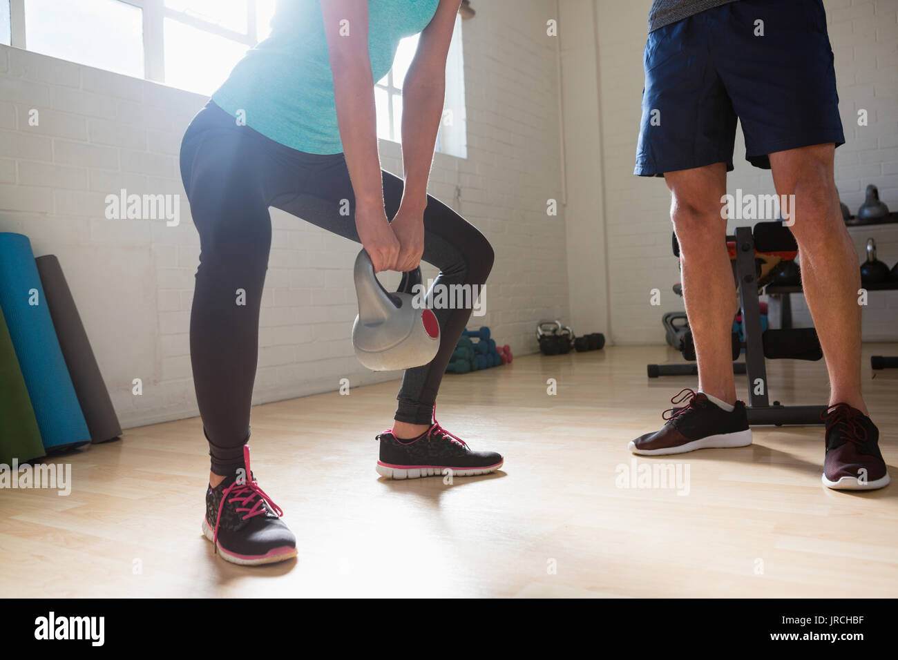 Low section of female athlete lifting kettlebells while standing by trainer in gym - Stock Image
