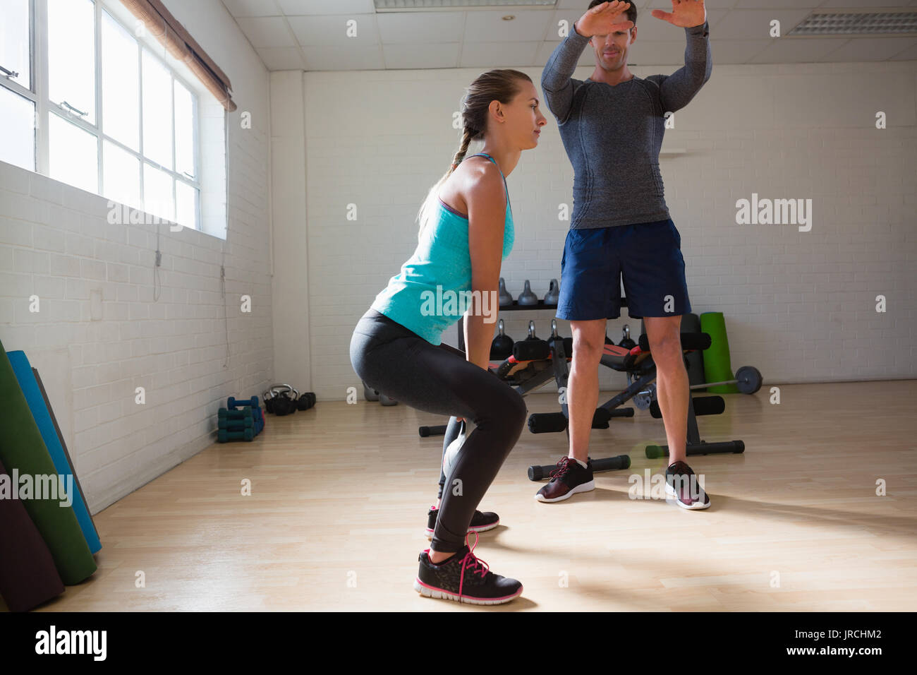 Male trainer training woman in lifting kettlebells at fitness studio - Stock Image