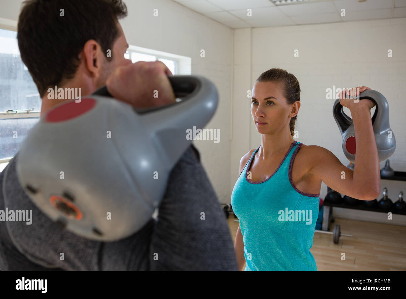 Athletes lifting kettlebells while facing each other in gym Stock Photo