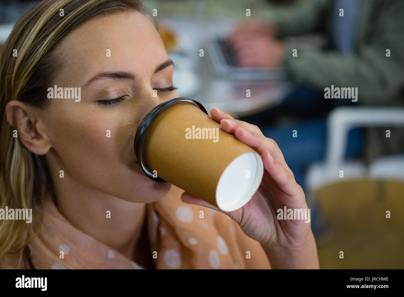 Close up of young woman with eyes closed having coffee at cafeteria - Stock Image