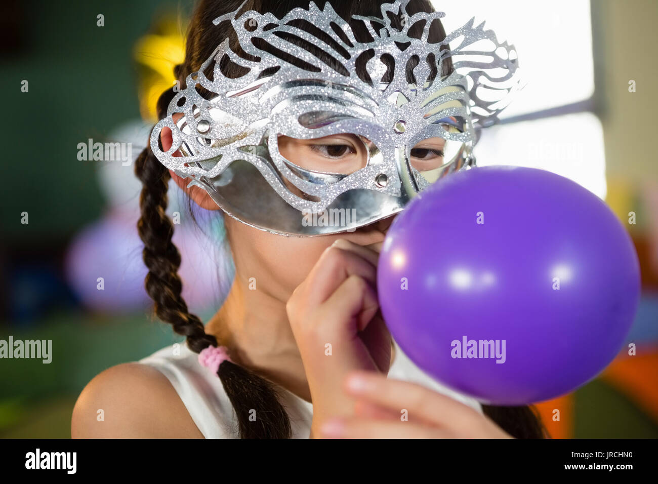 Adorable girl blowing balloon during birthday party at home - Stock Image