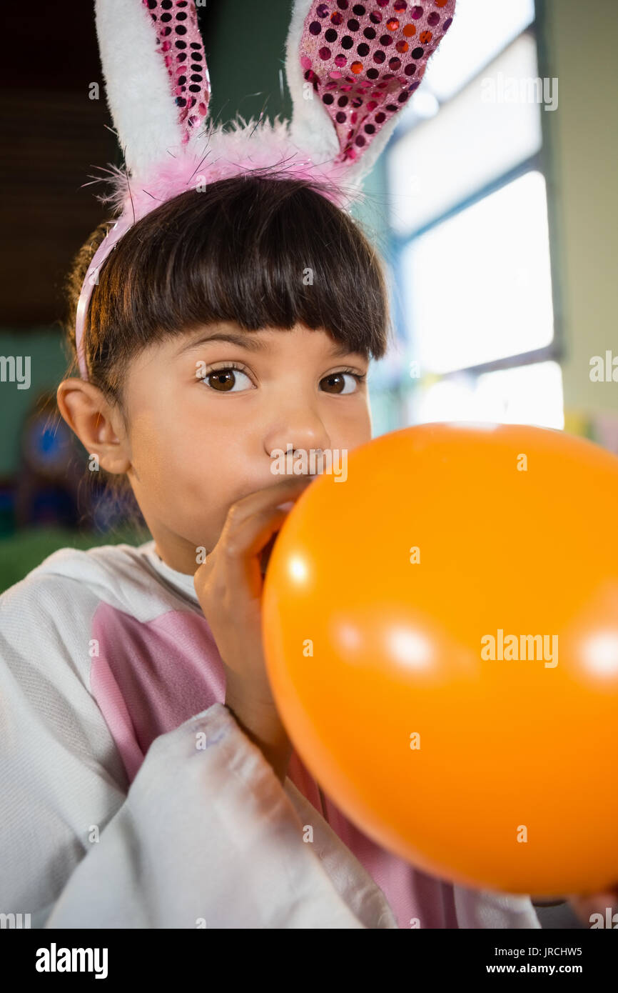 Portrait of girl blowing balloon during birthday party at home - Stock Image