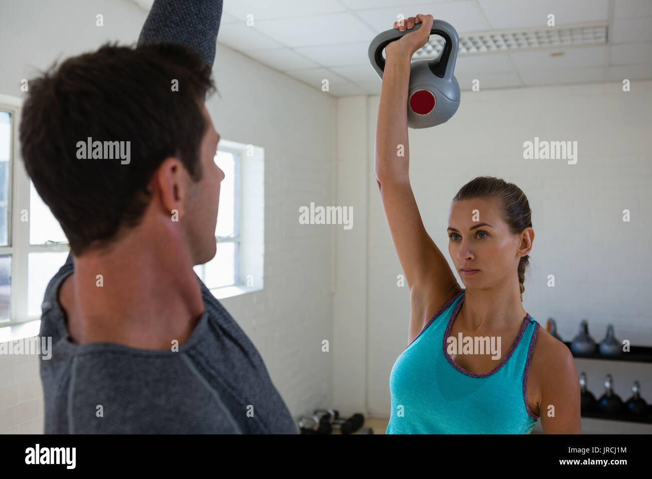 Confident athletes lifting kettlebells while facing each other in club Stock Photo
