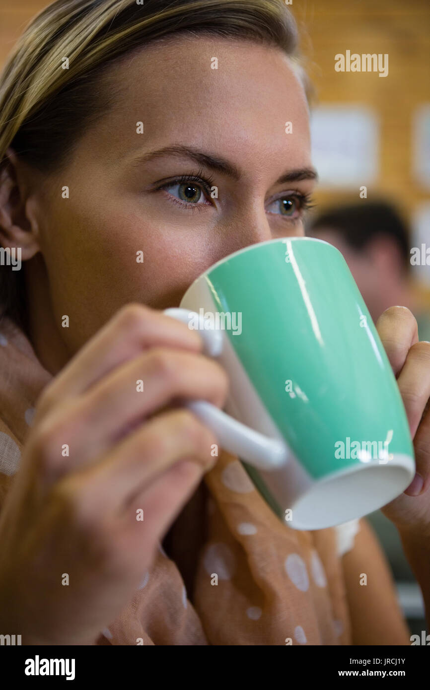 Close up of thoughtful young woman drinking coffee at cafe - Stock Image