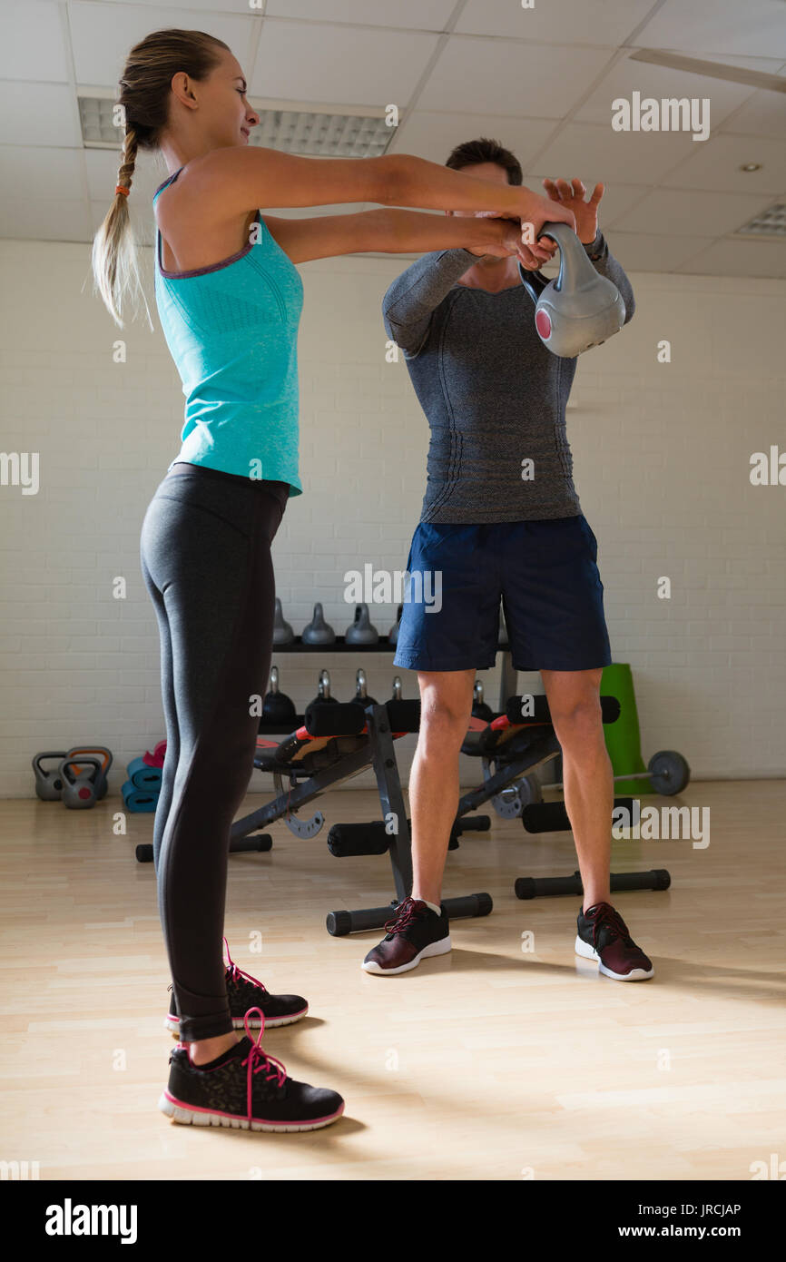 Male trainer training woman in lifting kettlebells at gym - Stock Image