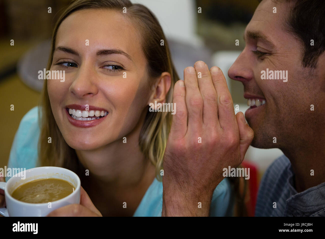 Happy man whispering into ears of girlfriend having coffee at cafe - Stock Image