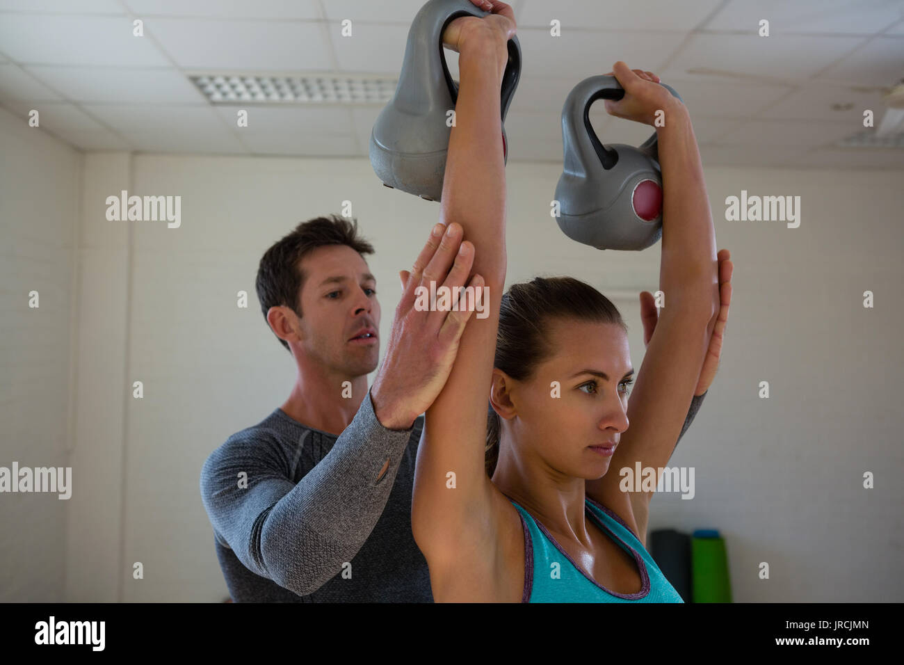 Trainer assisting female athlete in lifting kettlebells at gym - Stock Image