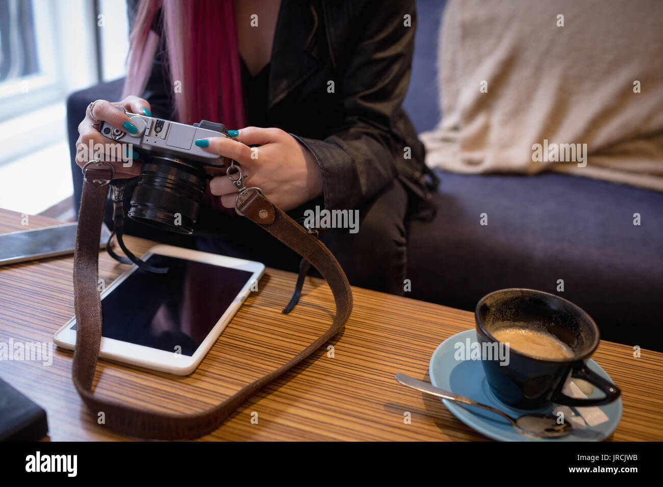 Mid section of woman reviewing pictures on digital camera in cafe - Stock Image
